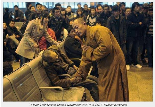 A monk prays for a dead man in the station hall of the Shanxi Taiyuan Train Station, China. The man died suddenly of natural causes while waiting for a train.